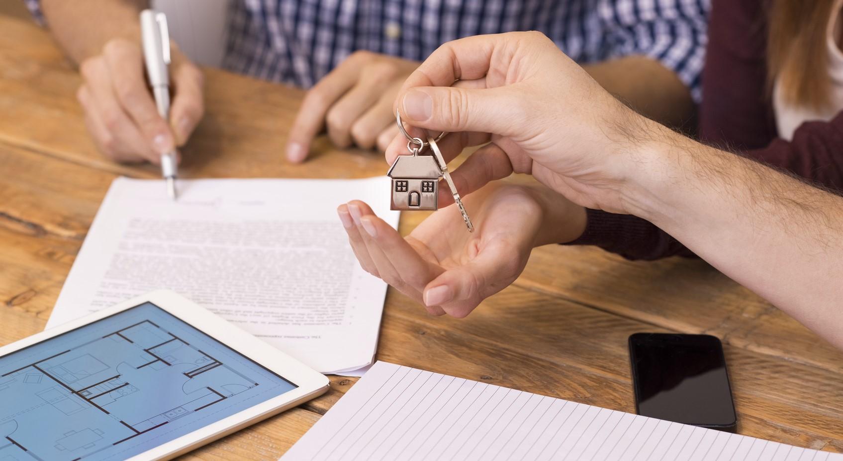 Ein Mann unterschreibt einen Kaufvertrag für eine Wohnung, während seine Frau die Schlüssel entgegennimmt.