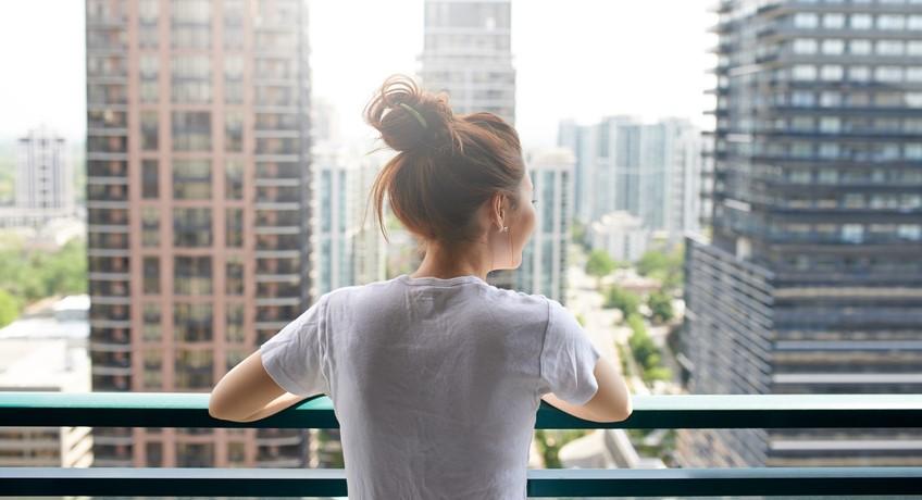 Eine junge Frau genießt den Ausblick auf ein modernes Wohnviertel.