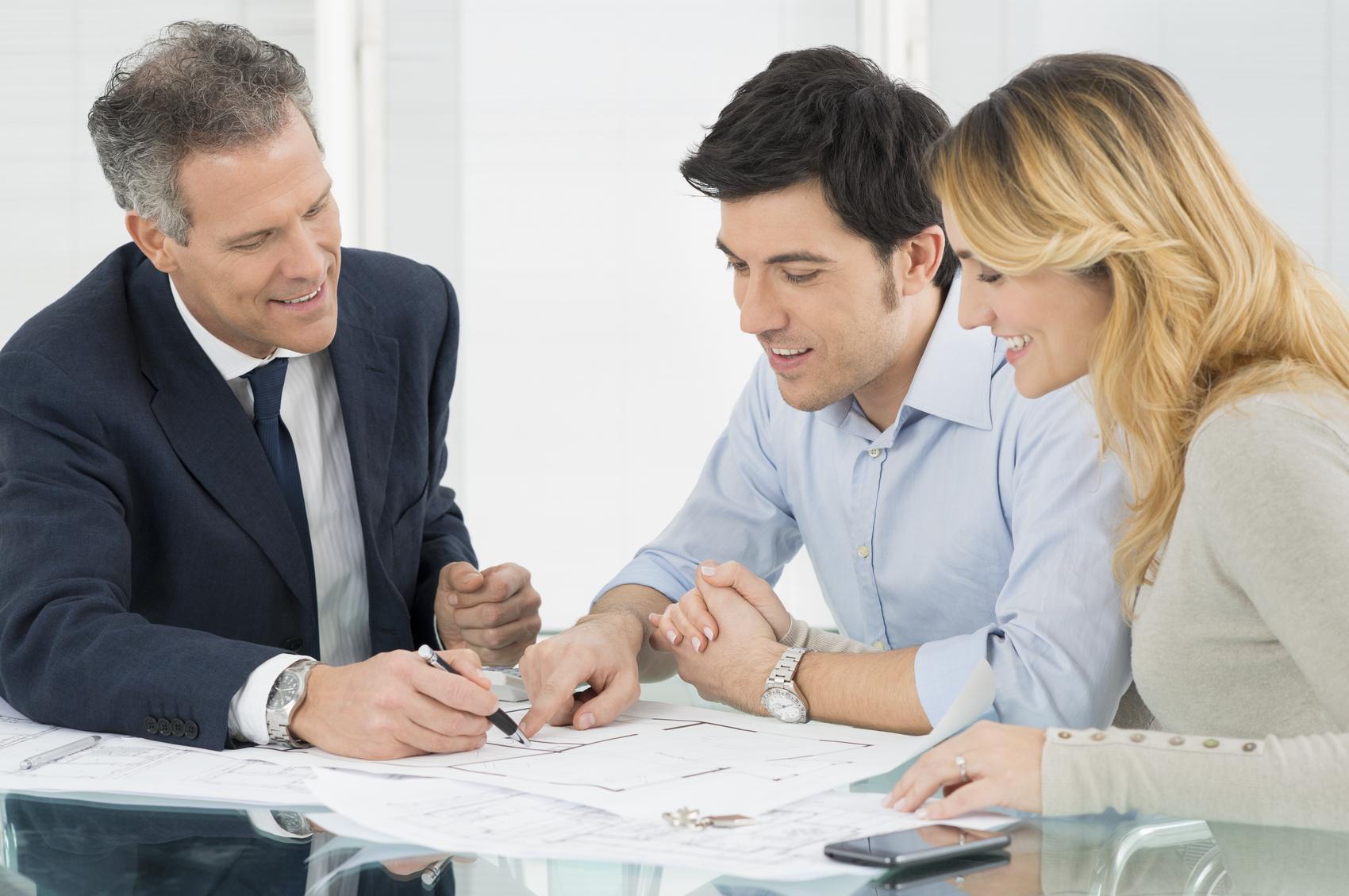 Ein junges Paar lässt sich von einem Bankkaufmann über eine Kapitalanlage beraten.