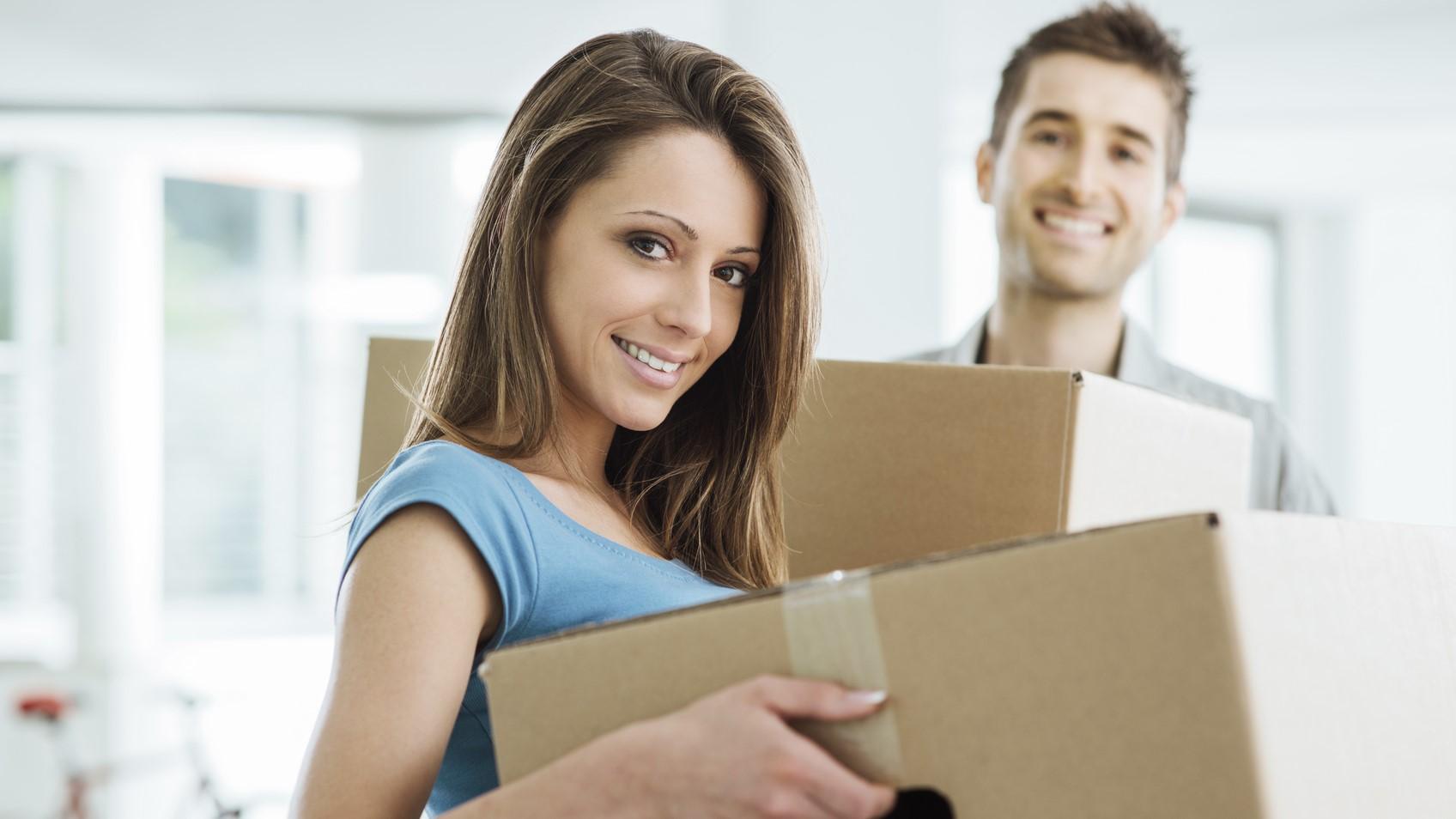 Ein junges Paar zieht in eine leere Wohnung ein.