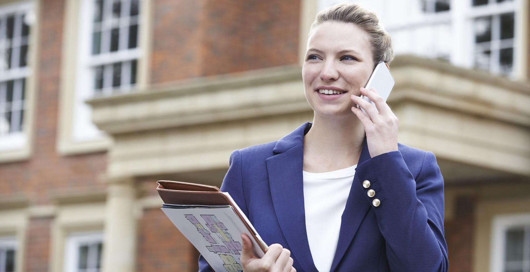 Eine junge Immobilienmaklerin steht vor einem Haus und telefoniert.